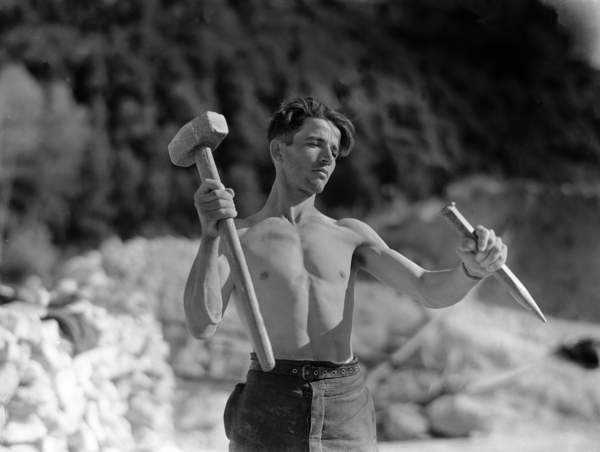 a bare-chested young worker with mallet and a chisel in Laconi Cave, Italy 1940-50 (b/w photo)
