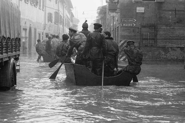 Soldiers rowing on a small boat rescuing people stranded by the flood of Florence, November 1966 (b/w photo)
