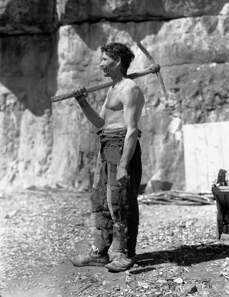 Old Bare-chested worker with a pick on his shoulder in a cave. The photograph was commissioned by the ILVA factory of Genoa
