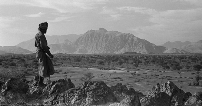 View of a member of Wilfred Thesiger's travelling party looking out across the Wadi Sayfam towards Jebel Kawr, Oman, March 30 – April 2, 1949 (b/w photo), Wilfred Patrick Thesiger, (1910-2003) / Pitt Rivers Museum, Oxford, UK