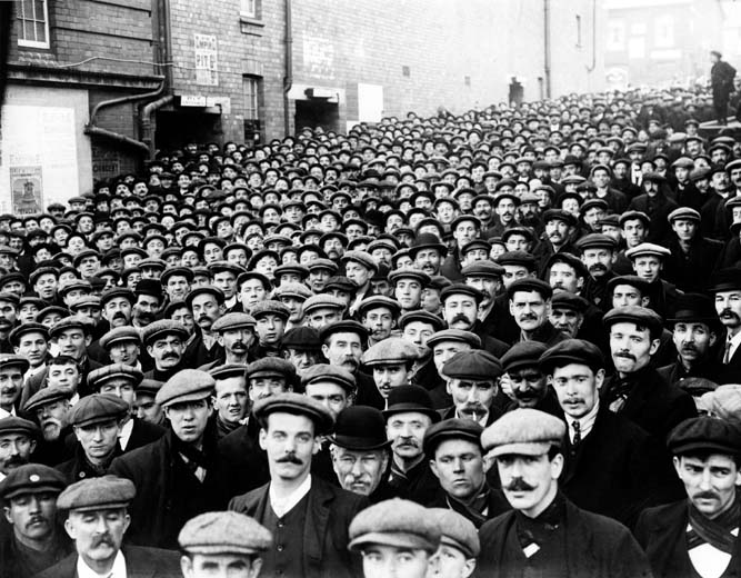 Miners waiting to go into the mass meeting at Empire Theatre, Tonypandy on the 9th November 1910 National Museum Wales