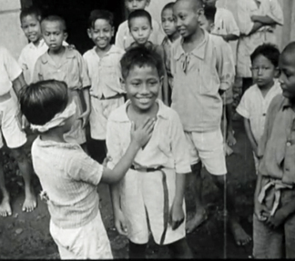 Indonesian children playing 'Blind Man's Bluff' at the opening of their new school, 1945 / Netherlands Institute for Sound and Vision / Bridgeman