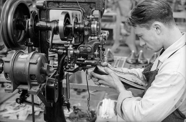 Closeup of a young worker to sew a shoe with the help of a machine inside the shoe factory Montanari, Italy, 50's 60's