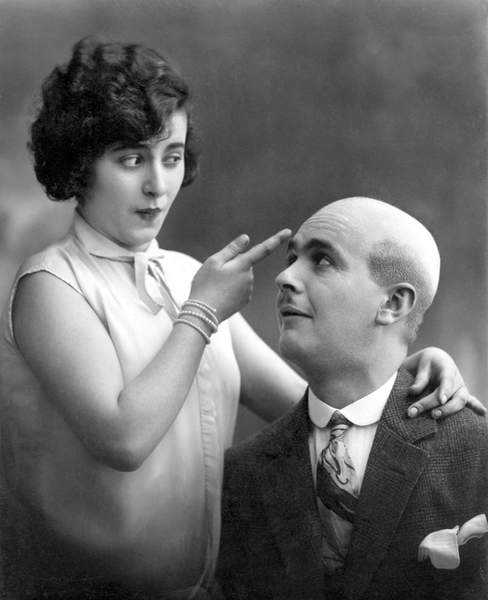 "Woman showing with one finger the skull of a bald man: ""Why does Egon have no hair? """" . Photography around 1920 / Photo © Imagebroker / Bridgeman Images"