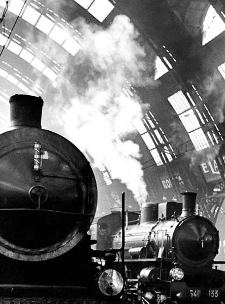 old locomotives with steam coming out inside a station in Italy, black and white photo