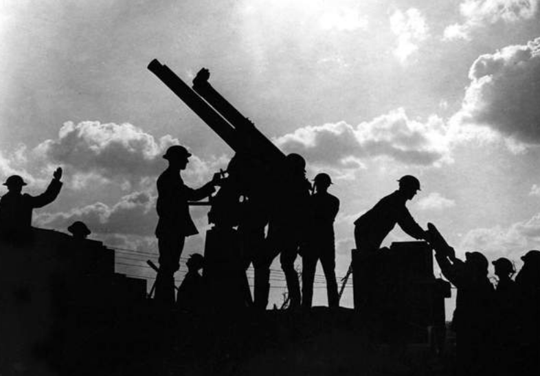 Images of WWI BATTLES Soldiers silhouetted against the sky prepare to fire an anti-aircraft gun.